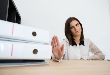 Young business woman sitting at table saying NO